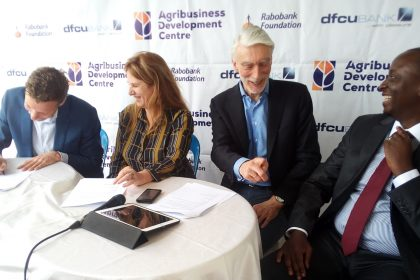Van den Bosch (left) puts pen to paper together with Feijter witnessed by Moll and dfcu Bank executive director, William Sekabembe